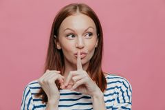 Pretty curious Caucasian woman makes silence sign, keeps index finger over mouth, looks secretly aside, wears striped casual. Clothes, poses over pink studio royalty free stock photography