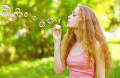 Pretty curly girl blowing soap bubbles having fun outdoors Stock Images