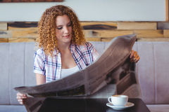 Pretty curly hair girl having cup of coffee and reading newspaper Stock Photos