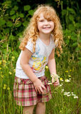 Pretty curly haired girl picking flowers Royalty Free Stock Photo