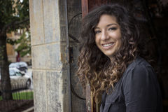 Pretty Curly Haired Woman in Restaurant Doorway Royalty Free Stock Photography