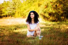 Pretty curly woman posing on grass in sunny royalty free stock photos