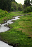Pretty Curvy Creek. A small peaceful pretty curvy creek meanders through a low wet land royalty free stock images