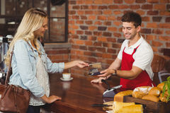 Pretty customer making a mobile payment Royalty Free Stock Photos