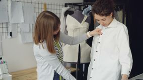 Pretty customer is trying on tailored shirt and sharing her opinion while clothing designer is measuring and checking. Pretty customer is trying on tailored stock video footage