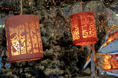 Pretty cut-outs on pink lanterns lit for a cold Winter night. Pretty pink lanterns with intricate details of cut-outs, with soft lighting, hung in the windows of stock photos