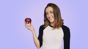 Cute and pretty woman holds tasty juicy apple. Pretty cute and beautiful young female with healthy lifestyle habits and eating organic biological food, holds stock video footage