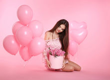 Pretty cute brunette girl with balloons and bouquet of rose flow Royalty Free Stock Images