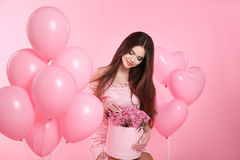 Pretty cute brunette girl with balloons and bouquet of rose flow Stock Photo