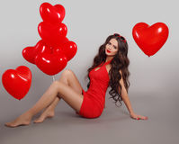 Pretty cute brunette girl in red dress with heart shape balloons. Sitting in love isolated on gray studio background. Valentine day. Birthday party Royalty Free Stock Image