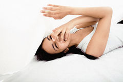 Pretty cute brunette woman in bed under sheets Stock Photography