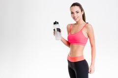 Pretty cute cheerful fitness girl holding a bottle of water. Pretty cute cheerful fitness girl in pink top and black leggings holding a bottle of water over Stock Photography