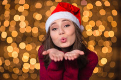 Pretty cute curly girl in santa claus hat sending kisses Stock Image