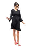 Pretty cute fashion model in black dress walking and balancing looking down. Stock Image