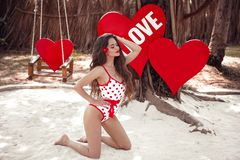 Pretty cute girl model in pinup style swimwear posing on white sand, over hearts. Maldives concept. Valentines day royalty free stock photos