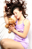 Pretty cute girl sleeping with teddy bear. Beautiful young woman in the morning in bed Royalty Free Stock Photo