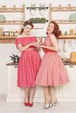 Beautiful elegant retro women standing in their kitchen and smiling stock image