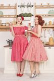 Beautiful elegant retro women standing in their kitchen and smiling. Pretty cute joyful ladies wearing red vintage clothes and having fun in their white kitchen stock photos