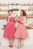 Beautiful elegant retro women standing in their kitchen and smiling. Pretty cute joyful ladies wearing red vintage clothes and having fun in their white kitchen stock images
