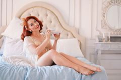 A luxurious pin up lady dressed in a beige vintage lingerie posing in her bedroom and have a cup of breakfast tea. Pretty cute joyful lady wearing vintage royalty free stock image