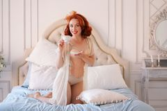 A luxurious pin up lady dressed in a beige vintage lingerie posing in her bedroom and have a cup of breakfast tea. Pretty cute joyful lady wearing vintage royalty free stock photography