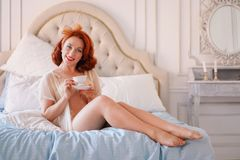 A luxurious pin up lady dressed in a beige vintage lingerie posing in her bedroom and have a cup of breakfast tea. Pretty cute joyful lady wearing vintage royalty free stock images