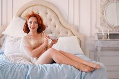 A luxurious pin up lady dressed in a beige vintage lingerie posing in her bedroom and have a cup of breakfast tea. Pretty cute joyful lady wearing vintage stock image
