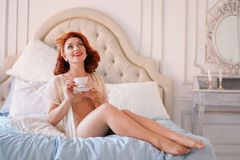 A luxurious pin up lady dressed in a beige vintage lingerie posing in her bedroom and have a cup of breakfast tea. Pretty cute joyful lady wearing vintage stock photo