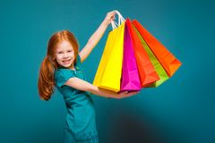 Pretty, cute little girl in blue clothes with long red hair cares different packages Royalty Free Stock Photos