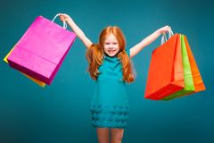 Pretty, cute little girl in blue clothes with long red hair cares different packages Royalty Free Stock Photo