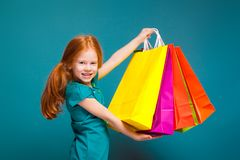 Pretty, cute little girl in blue clothes with long red hair cares different packages Stock Photos