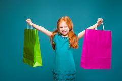 Pretty, cute little girl in blue clothes with long red hair cares packages Royalty Free Stock Images