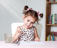 Pretty and cute little girl painting picture with watercolor in studio. Concept of education process Stock Images