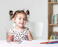 Pretty and cute little girl painting picture with watercolor in studio. Concept of education process. stock images