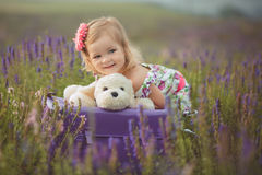 Pretty cute little girl is wearing white dress in a lavender field holding a basket full of purple flowers Royalty Free Stock Images
