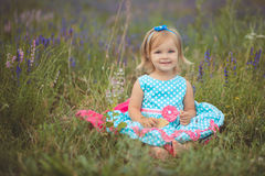 Pretty cute little girl is wearing white dress in a lavender field holding a basket full of purple flowers Royalty Free Stock Photo