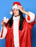 Pretty cute sexy santa girl. Or brunette woman with close eyes in new year sweater and christmas or xmas hat holds pink piggy pig bank on blue studio background Stock Image