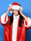 Pretty cute sexy santa girl. Or brunette woman with close eyes in new year sweater and christmas or xmas hat holds pink piggy pig bank on blue studio background Royalty Free Stock Photo