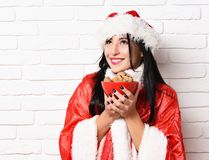 Pretty cute sexy santa girl. Or smiling happy brunette woman in new year sweater and hat holds christmas or xmas chocolate ?hip cookies in bowl on white brick Royalty Free Stock Image