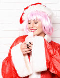 Pretty cute sexy santa girl. Or smiling brunette woman in new year red sweater and christmas or xmas hat in pink wig holds piggy pig bank on white brick wall Royalty Free Stock Photo