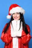 Pretty cute sexy santa girl. Or smiling brunette woman in new year sweater and christmas or xmas hat on blue studio background Royalty Free Stock Photos