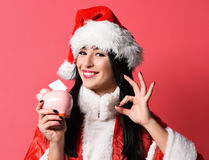 Pretty cute sexy santa girl. Or smiling brunette woman in new year sweater and christmas or xmas hat holds pink piggy pig bank and showing ok on red studio Stock Image