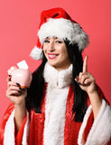 Pretty cute sexy santa girl. Or smiling brunette woman in new year sweater and christmas or xmas hat holds pink piggy pig bank with raised finger on red studio Stock Photos
