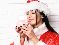 Pretty cute sexy santa girl. Or smiling brunette woman in new year sweater and christmas or xmas hat holds pink piggy pig bank on white brick wall background Royalty Free Stock Images