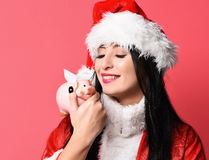 Pretty cute sexy santa girl. Or smiling brunette woman in new year sweater and christmas or xmas hat holds pink piggy pig bank on red studio background Royalty Free Stock Photography