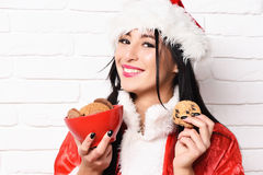 Pretty cute sexy santa girl. Or smiling brunette woman in new year sweater and hat holds christmas or xmas chocolate ?hip cookies in bowl on white brick wall Royalty Free Stock Photo