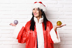 Pretty cute sexy santa girl. Or smiling brunette woman in new year sweater and hat holds christmas or xmas colorful balls on white brick wall background Royalty Free Stock Photos
