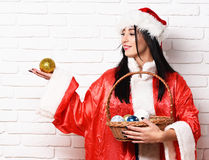 Pretty cute sexy santa girl. Or smiling brunette woman in new year sweater and hat holds christmas or xmas colorful bucket with balls on white brick wall Stock Photo