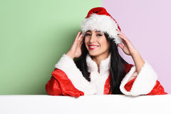 Pretty cute sexy santa girl. Or smiling brunette woman in red sweater and christmas or xmas hat on purple green studio background Royalty Free Stock Images