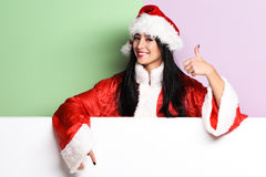 Pretty cute sexy santa girl. Or smiling brunette woman in red sweater with christmas or xmas hat and showing cool on purple green studio background Royalty Free Stock Image